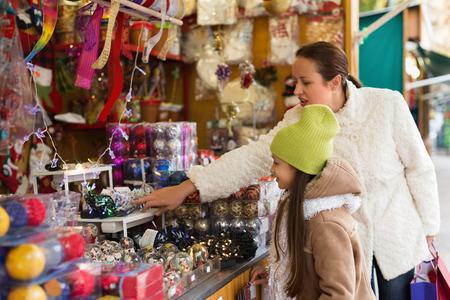 overspending: Little smiling girl with mom in Christmas market. Focus on girl