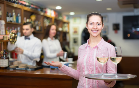 Smiling waitress with beverages and bar crew at background Stock Photo