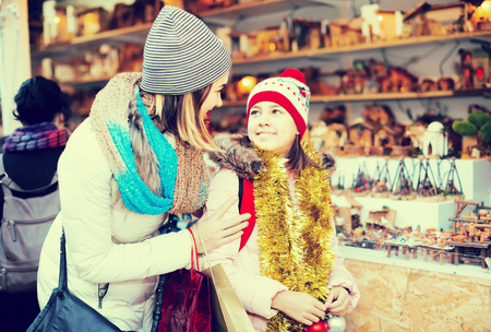 overspending: Little girl with cheerful mom buying figures and workpiece for creating Christmas scenes at an open air market
