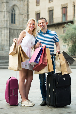 Cheerful young couple looking satisfied after shopping and carrying few paper bags outdoors Stock Photo