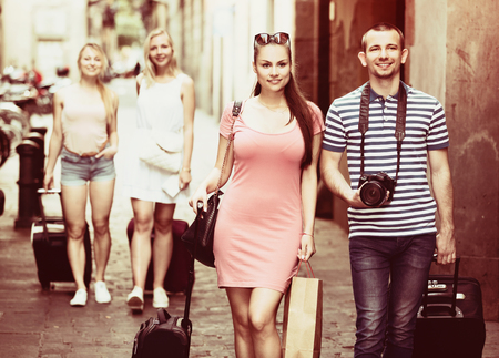 strret: Couple travellers and two friends girls going down european strret with luggage on summer vacation