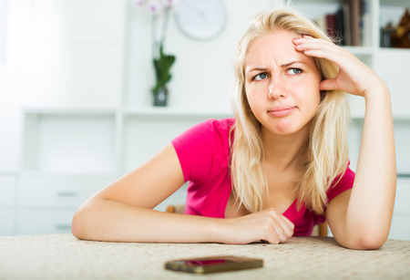 Woman looking annoyed and waiting for call on mobile phone indoors
