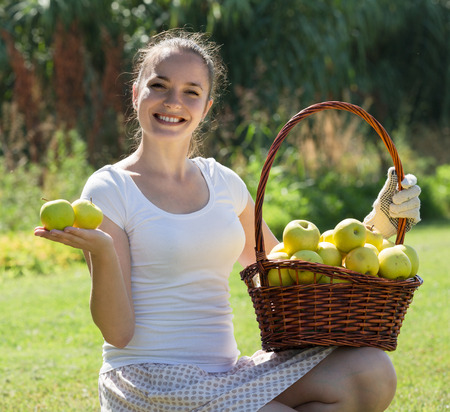 Smiling young woman with basket of apples in the garden