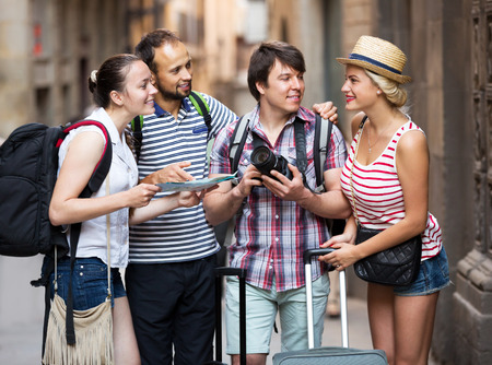 Positive company of impressed travelers during city walking Stock Photo
