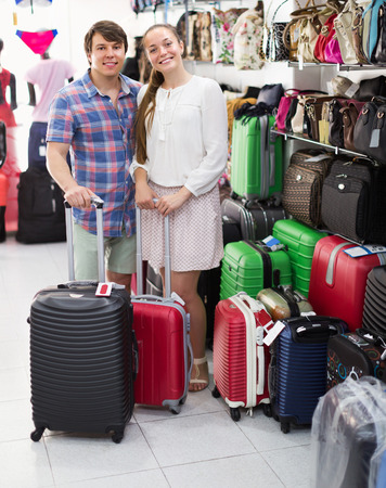 Happy young pair shops at the store choosing suitcase Stock Photo