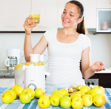 domestic kitchen: Young smiling woman preparing fresh apple juice in domestic kitchen