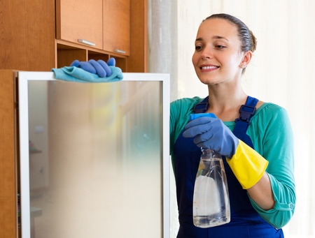 Young smiling female cleaner making cleaning in the office-room