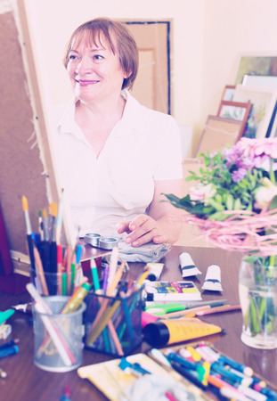 contentedness: Cheerful senior woman painting a new picture Stock Photo