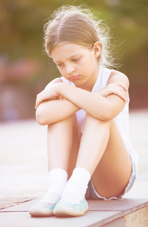 Lonely girl in elementary school age crying and feeling confused outdoors Stock Photo
