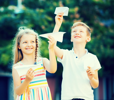niÑos contentos: two glad children playing with paper planes in town on summer day Foto de archivo