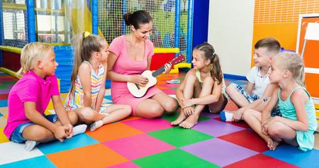 niÑos contentos: Niños sonrientes alegres que se sientan con el maestro de la celebración de ukelele y escuchar música en clase en la escuela Foto de archivo