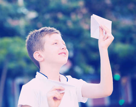 smiling boy in elementary school age playing with flying paper planes outdoors Stock Photo