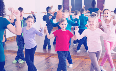 Vriendschappelijke lachende kinderen dansen samen in de studio lachend en plezier