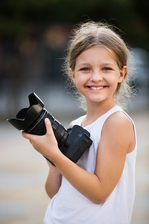 diligente: Smiling diligent girl taking pictures with professional camera outdoors on summer day Foto de archivo