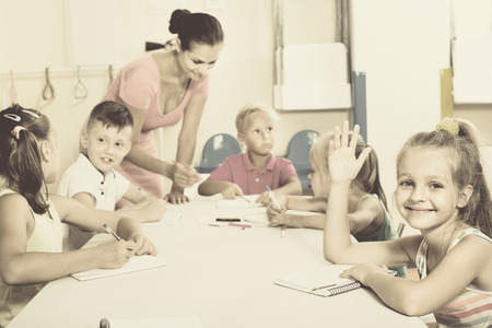 diligente: Cheerful diligent kids learning to write on lesson in elementary school class