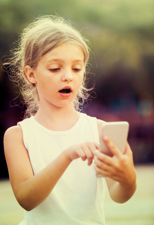 gasping: girl in elementary school age is very surprised while looking at mobile phone outdoors