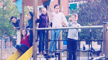 niÑos contentos: Smiling  glad children in school age sliding down together on playgrounds construction at street