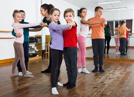 niÑos contentos: Happy glad  children studying of partner dance  at dance school