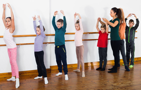 Young cheerful positive ballet dancers exercising in ballroom Stock Photo
