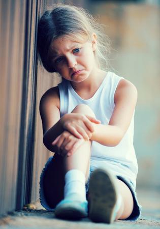 loser: girl in elementary school age looking depressed outdoors in park