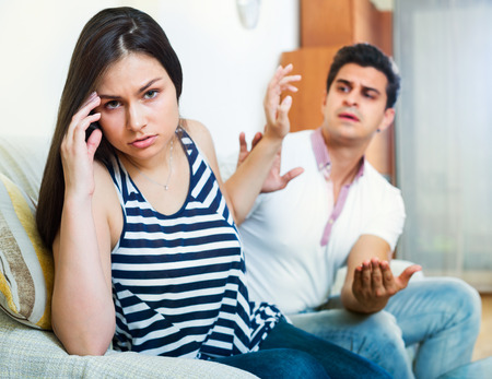 Angry young spouses having domestic argue at a living room Stock Photo