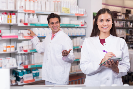 Professional smiling pharmaceutists at reception of drugstore ready to help Stock Photo