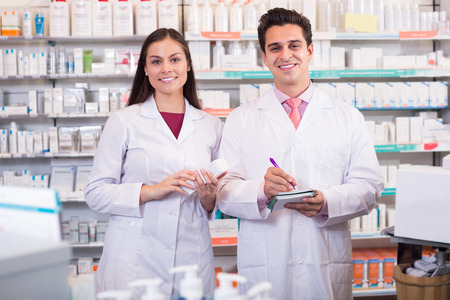portrait of smiling pharmacist and pharmacy technician posing in drugstore