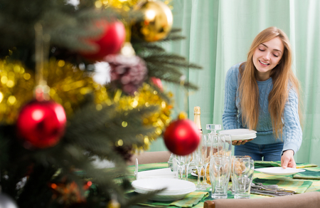 fizz: smiling woman, arranging Christmas table before guests coming