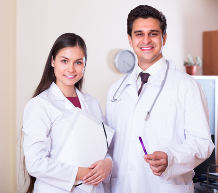 therapeutist: Portrait of smiling therapeutist with stethoscope and his assistant in private clinic Stock Photo