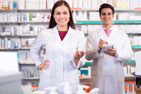 Portrait of two cheerful friendly pharmacists working in modern farmacy. Focus on the woman