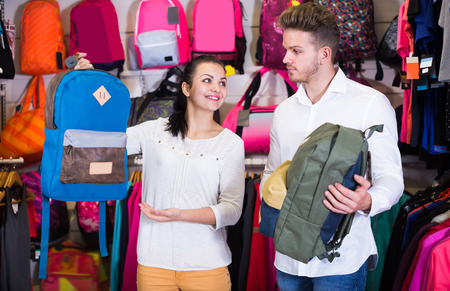 Young loving couple deciding on sports bag in sports store