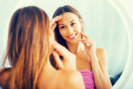 spanish woman: young positive spanish woman examining her face by looking at it in mirror