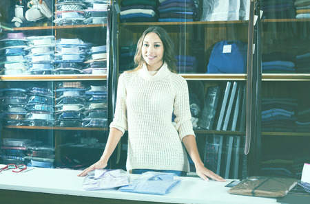 young female shopping assistant offering various shirts in men�s cloths store