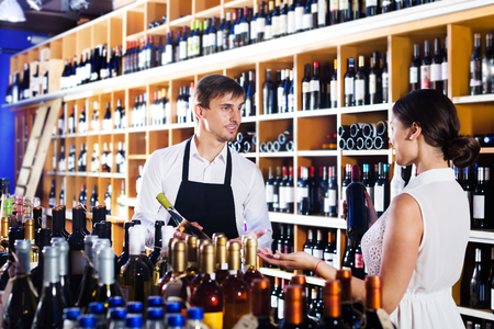 Young man seller wearing uniform helping woman customer with a bottle of wine at wine house