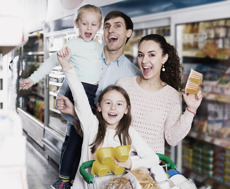 Young parents with two kids buying fruit yoghurt and pudding