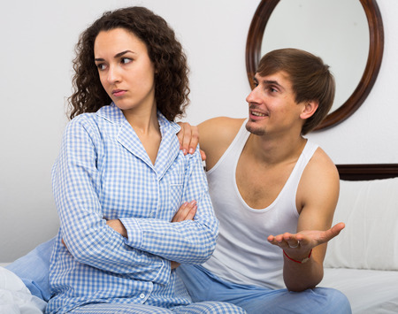 offended: Offended curly girl and man trying to reconcile in bed