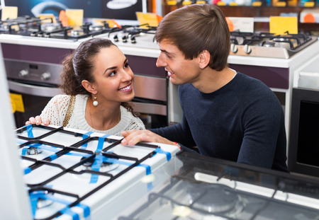 hobs: Ordinary couple choosing model of gas hobs in hypermarket and smiling