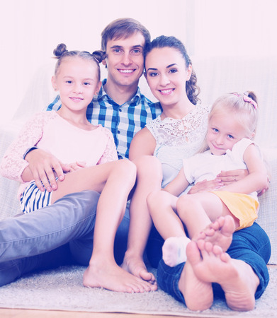 Beautiful young parents with two daughters relaxing at home Stock Photo