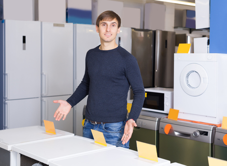 hobs: Young man posing at household appliances section of supermarket Stock Photo