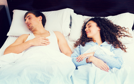 Handsome young man and brunette girlfriend sleeping at home Stock Photo