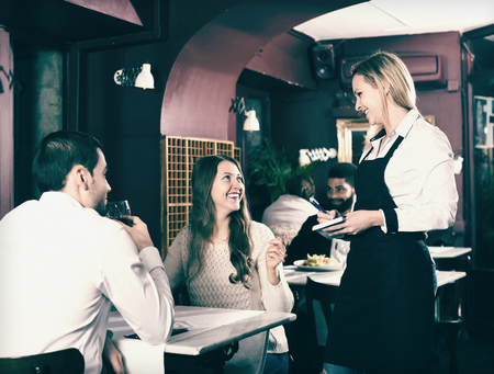 middle class: Smiling adult spouses having date in middle class restaurant. Focus on blonde girl Stock Photo