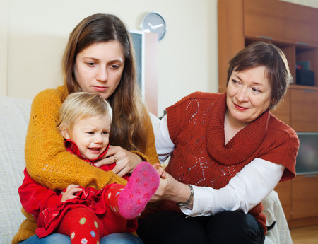 intergenerational: Conflict of intergenerational. Young mother with crying baby and grandmother after quarrel at home