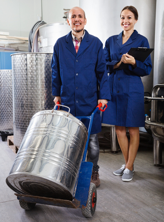 diligente: Portrait of cheerful diligent expert woman standing with clipboard and male winemaker in wine processing section