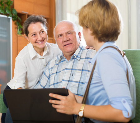 Mature smiling couple filling questionnaire for employee with laptop of the bank