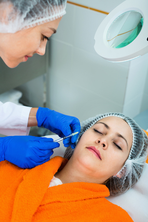 Smiling woman doctor making beauty injection to young female client