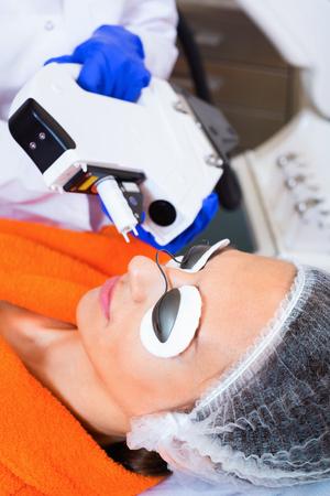 Mujer positiva alegre alegre que quita el pelo de la cara con el laser