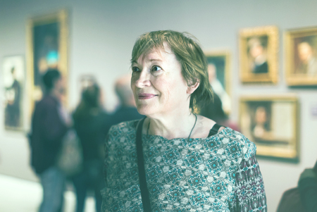 caucasian  pensioner woman watching at art collection exhibition in museum Stock Photo