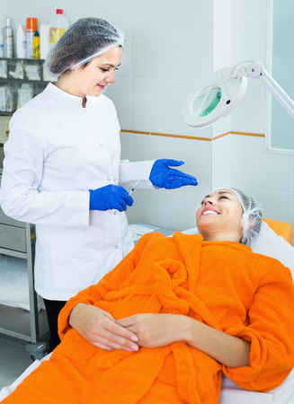 healthcare visitor: Young female doctor preparing to do beauty procedures to woman client Stock Photo