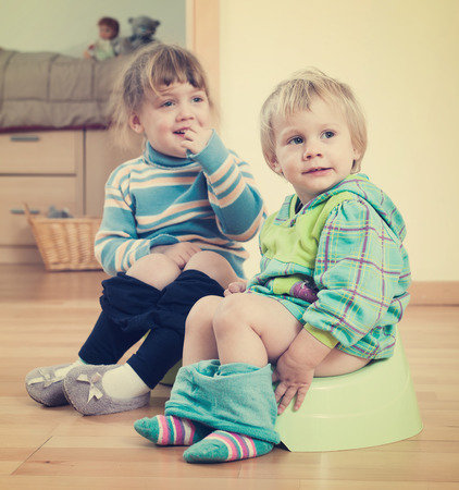 piddle: Two children sitting on bedpans in home interior Stock Photo