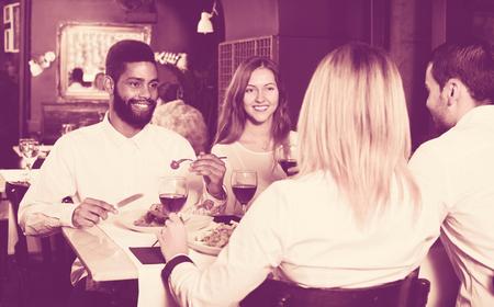 clase media: Gente de clase media felices disfrutando de la comida en la cafetería y hablando